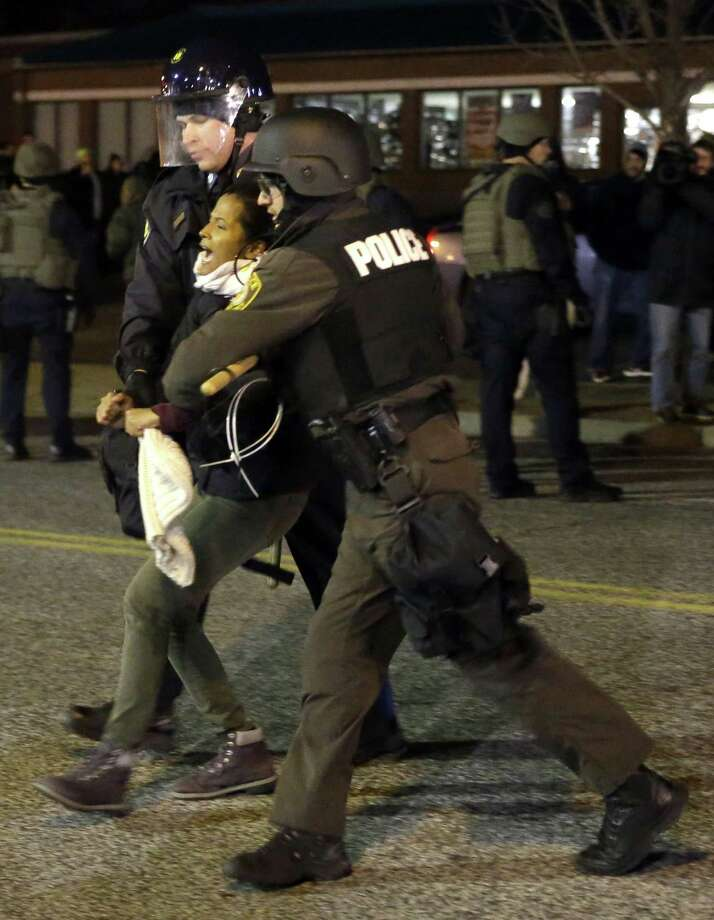 A protester is taken into custody Friday, Nov. 28, 2014, in Ferguson, Mo. Several protesters have been taken into custody during a demonstration outside the police department. Tensions escalated late Friday during an initially calm demonstration after police said protesters were illegally blocking West Florissant Avenue. (AP Photo/Jeff Roberson) Photo: AP / AP