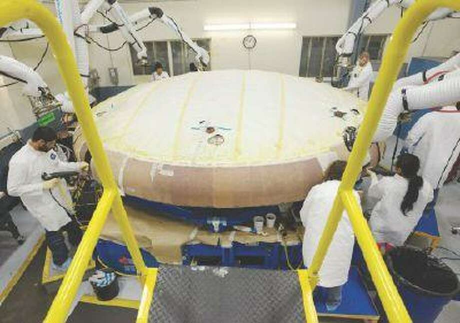 Workers at Textron Defense Systems in Wilmington, Mass., apply a coating to a heat shield that will attach to the Orion, a spacecraft scheduled to launch in 2017 and take astronauts farther in space than ever before.