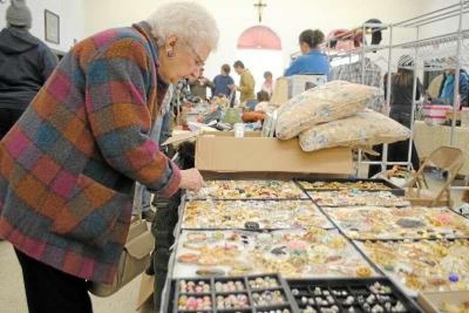 Jessica Glenza/Register Citizen A patron at the St. Thomas of Villanova Church flea market searches over broaches and pins.