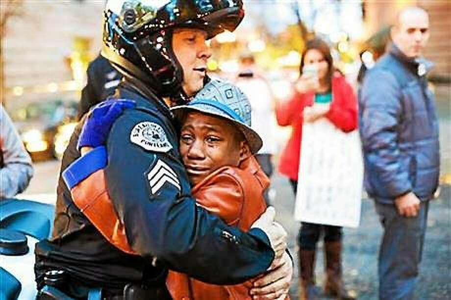 """A police officer in Portland, Ore., hugs a young protester who was carrying a sign that said, """"Free Hugs."""" Photo: (AP Photo/Johnny Huu Nguyen)"""