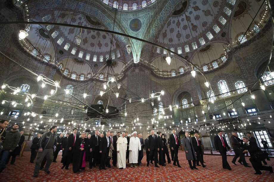 """In this photo provided by Vatican newspaper L'Osservatore Romano, Pope Francis and Grand Mufti of Istanbul, Rahmi Yaran visit the Sultan Ahmet mosque in Istanbul, Saturday, Nov. 29, 2014. Meeting with Turkish leaders in the capital Ankara a day earlier, Francis urged Muslim leaders to condemn the """"barbaric violence"""" being committed in Islam's name against religious minorities in Iraq and Syria. (AP Photo/L'Osservatore Romano) Photo: AP / L' Osservatore Romano"""