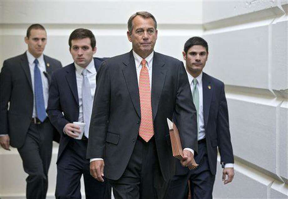 """House Speaker John Boehner of Ohio, who conferred with President Barack Obama yesterday by phone, walks to a closed-door meeting with the GOP caucus, Wednesday, Dec. 12, 2012, on Capitol Hill in Washington. Boehner and the other House Republican leaders are calling for Obama to come up with plan they can accept for spending cuts and tax revenue to avoid the so-called """"fiscal cliff"""" of automatic tax hikes and budget reductions. (AP Photo/J. Scott Applewhite) Photo: AP / AP"""