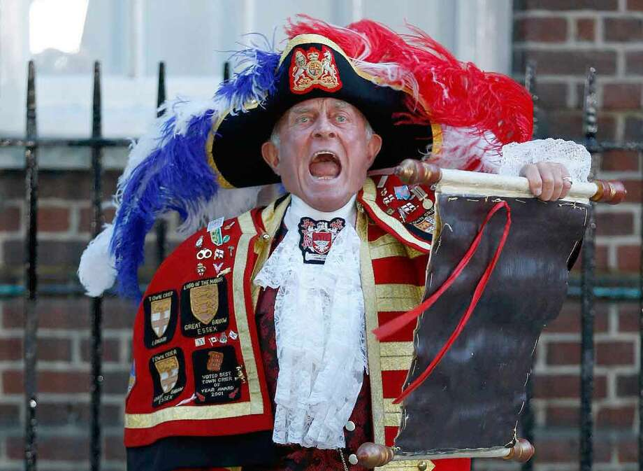 Tony Appleton, a town crier,  announces the birth of the royal baby, outside St. Mary's Hospital exclusive Lindo Wing in London, Monday, July 22, 2013. Palace officials say Prince William's wife Kate has given birth to a baby boy. The baby was born at 4:24 p.m. and weighs 8 pounds 6 ounces. The infant will become third in line for the British throne after Prince Charles and William. (AP Photo/Lefteris Pitarakis) Photo: ASSOCIATED PRESS / AP2013
