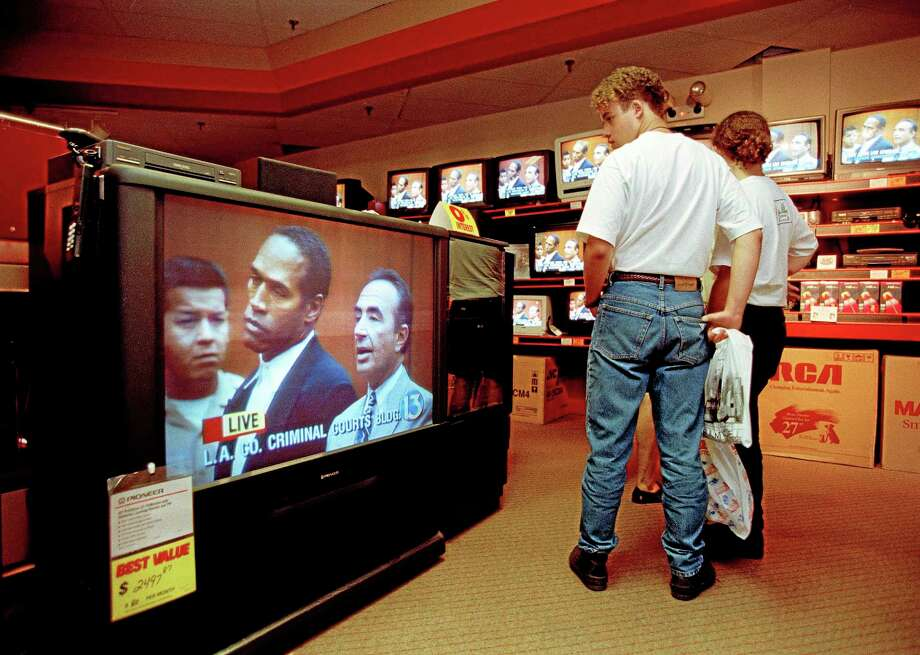 In this June 20, 1994 file photo, mall shoppers in Tampa, Fla., watch banks of televisions in an electronics store as the arraignment of O.J. Simpson is televised from Los Angeles. The O.J. Simpson trial was labeled the Trial of the Century and a forerunner of today's interactive media. Photo: AP Photo/Chris O'Meara, File  / AP