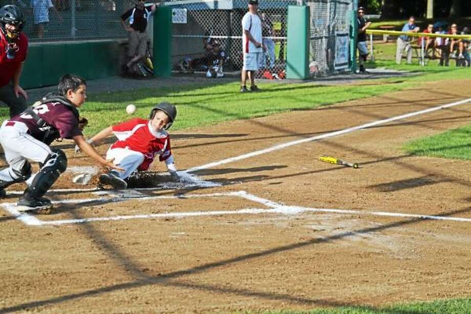 Pete Paguaga/Register Citizen  Jake Nilsson slides in safely in the first inning, scoring on a CJ sacrifice fly