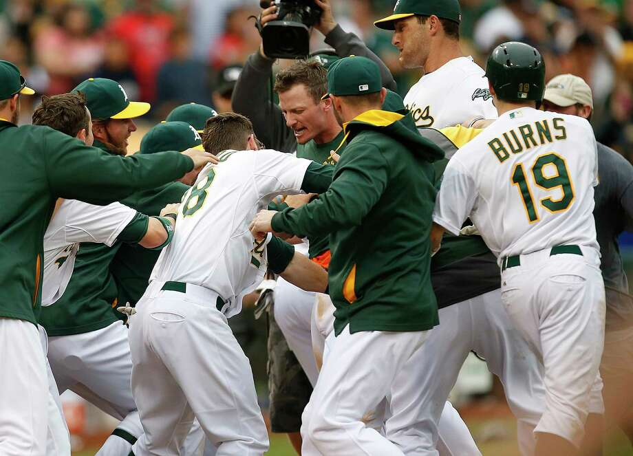 The Oakland Athletics traded Josh Donaldson, center, celebrating with teammates after hitting a two-run home against the Philadelphia Phillies in the 10th inning of a Sept. 21 game, to the Toronto Blue Jays for Brett Lawrie and prospects. Photo: Tony Avelar — The Associated Press File Photo  / FR155217 AP