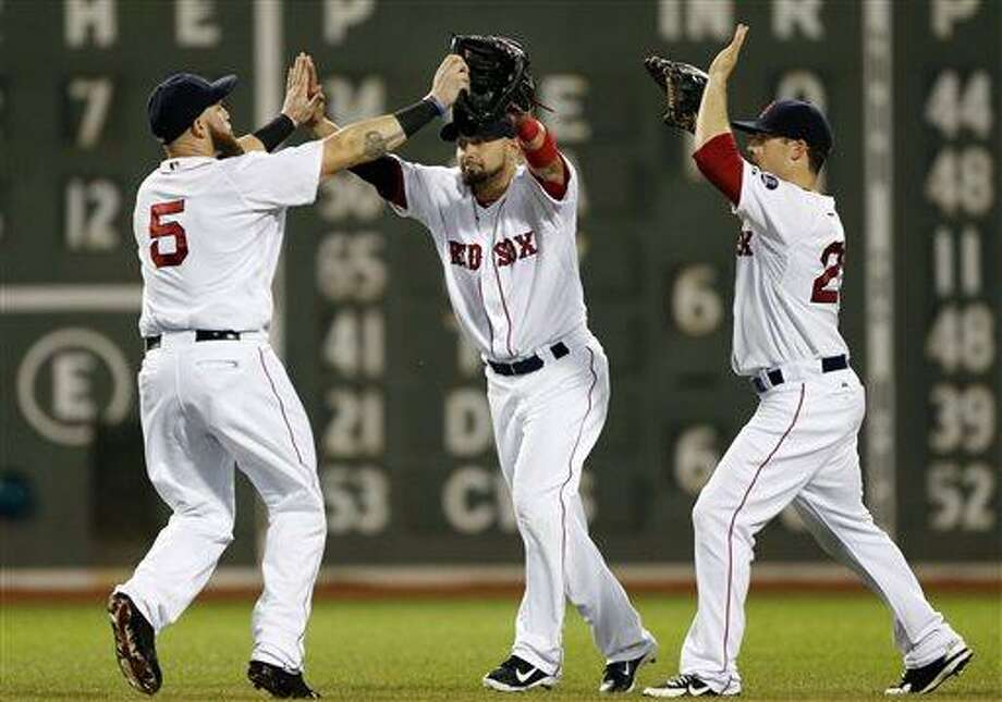 Boston Red Sox outfielders Jonny Gomes (5), Shane Victorino, middle, and Daniel Nava celebrate after the Red Sox defeated the Tampa Bay Rays 6-2 in a baseball game at Fenway Park in Boston Tuesday, July 23, 2013. (AP Photo/Elise Amendola) Photo: AP / AP