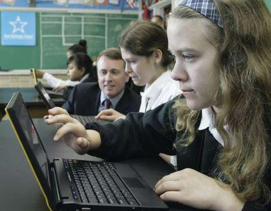 """Donovan Olsen, right, a sixth-grader at the Ann Richards School for Young Women Leaders, works on a new Dell """"netbook"""" Tuesday, May 19, 2009, in Austin, Texas. In the background, Paul Bell, left, president of Dell Global Public Sector Business, watches Karolyn Newton, center. (AP Photo/Harry Cabluck) Photo: AP / 2009 AP"""