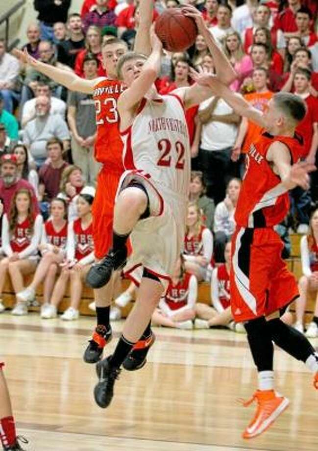 Northwestern's Jimi Phillips (22) shoots as Terryville's Sean Huria (23) tries for the block. Marianne Killackey/Special to Register Citizen / 2013