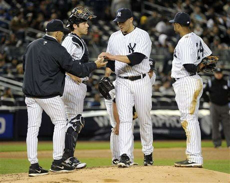 New York Yankees pitcher Andy Pettitte hands the ball to manager Joe Girardi, left, as Robinson Cano, right, and catcher Austin Romine look on during the fifth inning of a baseball game against the Houston Astros Monday, April 29, 2013, at Yankee Stadium in New York. (AP Photo/Bill Kostroun) Photo: ASSOCIATED PRESS / AP2013