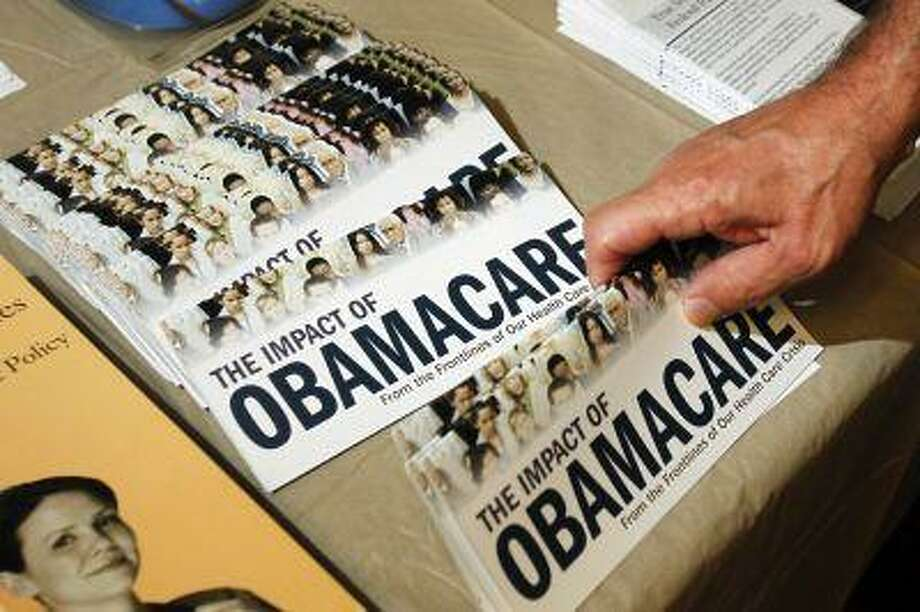 """A Tea Party member reaches for a pamphlet titled """"The Impact of Obamacare"""", at a """"Food for Free Minds Tea Party Rally"""" in Littleton, New Hampshire in this October 27, 2012 file photo. The Obama administration said on July 2, 2013 it would not require employers to provide health insurance for their workers until 2015, delaying a key provision of President Barack Obama's healthcare reform law by a year, to beyond the next election. REUTERS/Jessica Rinaldi//Files (UNITED STATES - Tags: POLITICS HEALTH) Photo: Reuters / X01704"""