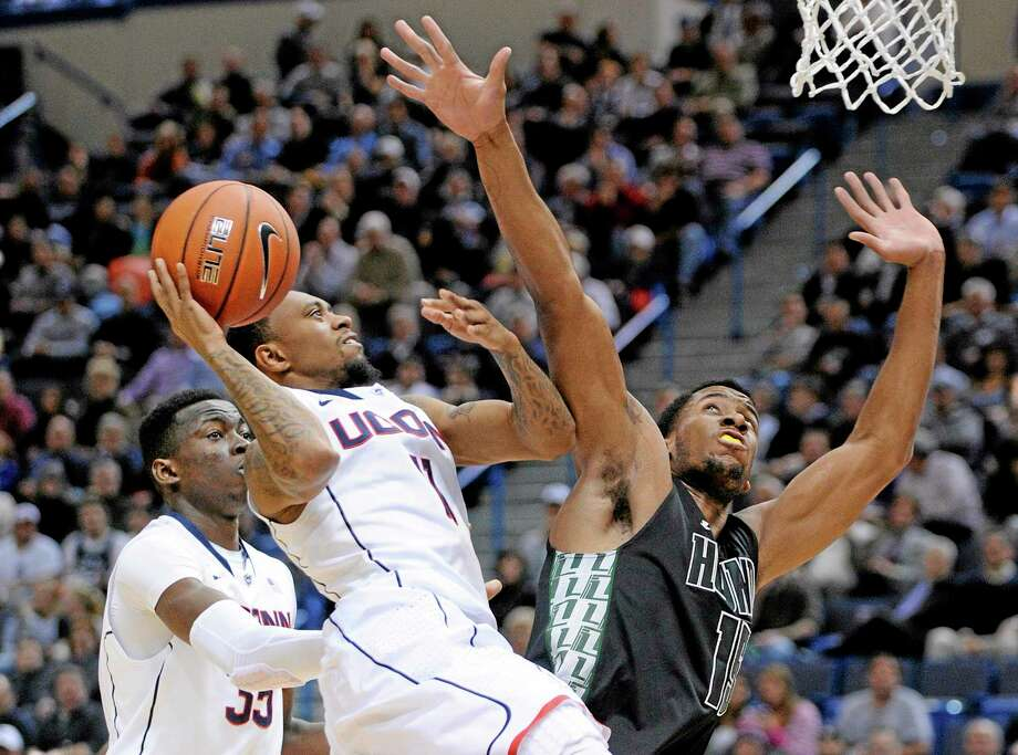 UConn guard Ryan Boatright. center, drives past Loyola forward Jordan Latham (15) during the first half of the 13th-ranked Huskies' 76-66 win Tuesday night at the XL Center in Hartford. Photo: Fred Beckham — The Associated Press  / FR153656 AP