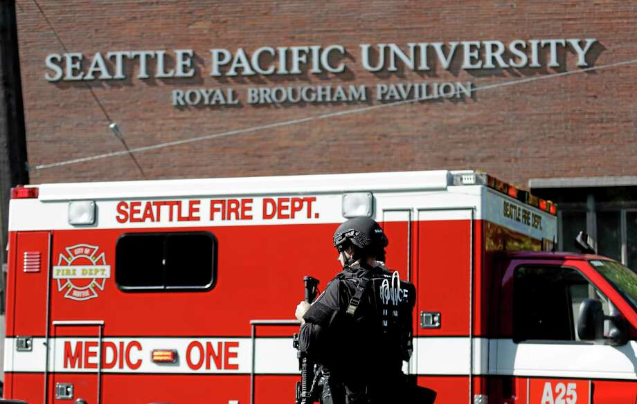 A Seattle police SWAT team member walks toward a campus building following a shooting at Seattle Pacific University on Thursday, June 5, 2014, in Seattle. A lone gunman armed with a shotgun opened fire in a building on the campus, killing one person before he was subdued by a student as he tried to reload, police said. Police say the student building monitor at the university disarmed the gunman and several other students held him until police arrived at the Otto Miller building. (AP Photo/Elaine Thompson) Photo: AP / AP