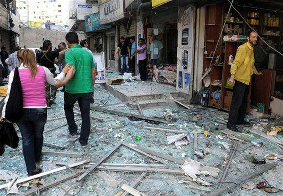 In this photo released by the Syrian official news agency SANA, Syrians walk on shattered glass from damaged shops at the scene of a powerful explosion which occurred in the central district of Marjeh, Damascus, Syria, Tuesday April 30, 2013. A powerful explosion rocked Damascus on Tuesday, causing scores of casualties, a day after the country's prime minister narrowly escaped an assassination attempt in the heart of the heavily protected capital. (AP Photo/SANA) Photo: ASSOCIATED PRESS / AP2013