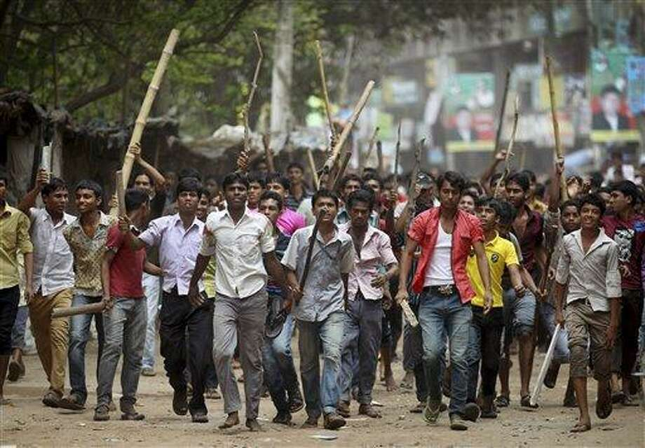 """Protestors march down a street demanding the death penalty for those responsible for the collapsed garment factory building, killing hundreds, Tuesday, April 30, 2013 in Savar, near Dhaka, Bangladesh.  A top Bangladesh court on Tuesday ordered the government to """"immediately"""" confiscate the property of a collapsed building's owner, as thousands of protesters demanding death penalty for the man clashed with police, leaving 100 people injured. (AP Photo/Wong Maye-E) Photo: AP / AP"""