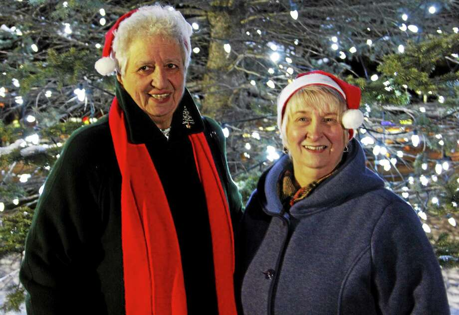 From left: Evelyn Lukes and Gloria Novak pose for a photo after helping light up the Coe Memorial Park tree on Friday, Nov. 28, in Torrington. Photo: Esteban L. Hernandez — Register Citizen