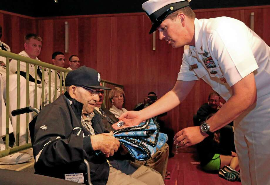 Baseball Hall of Famer Yogi Berra is presented with a quilt and a medal by Cmdr. Jim Wallace during a D-Day presentation at the Yogi Berra Museum Friday in Montclair, New Jersey. Berra served in the Navy 70 years ago as part of the D-Day invasion. Photo: Rich Schultz — The Associated Press  / FR27227 AP