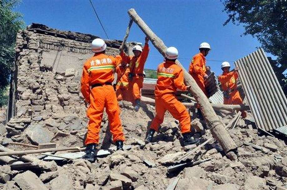 In this photo released by Xinhua News Agency, rescuers clear the debris of a damaged house in quake-hit Majiagou Village of Minxian County, northwest China's Gansu Province, Monday, July 22, 2013.  The toll of dead and injured continues to rise after an earthquake struck a dry, hilly farming area in western China early this morning. (AP Photo/Xinhua, Guo Gang) NO SALES Photo: AP / XinHua