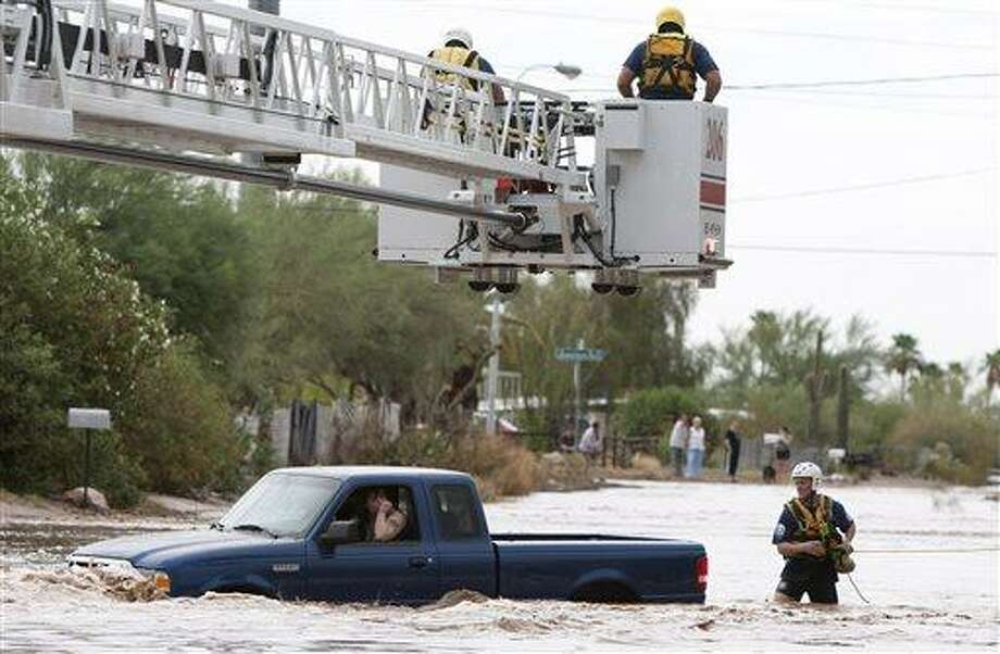 A man and woman sit in a truck on Tomahawk Rd. flooded by rain waters in Apache Junction, Ariz., Sunday, July 21, 2013. Mesa Fire Dept. were able to walk the two out safely. (AP Photo/The Arizona Republic, Cheryl Evans) Photo: AP / The Republic
