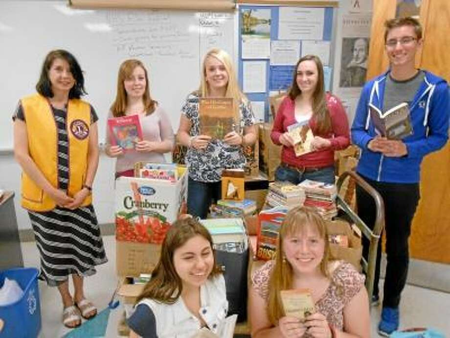 Members of the Lewis Mills High School Leo Club pose for a photo on Tuesday, April 30, 2013, with some of the books they collected during a three-week book drive in Burlington. The group, whose members are also part of the Humanitarian Club, collected more than 1,000 books for local libraries and hospitals. (REGISTER CITIZEN/DOUG MORROW)