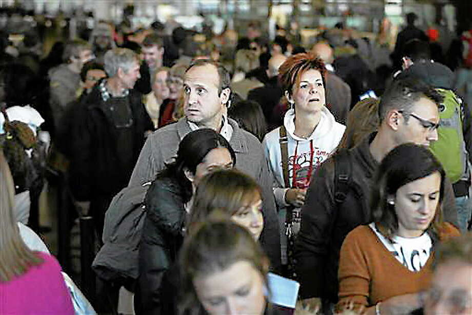 Travelers wait in a winding line to pass through customs and border control at John F. Kennedy International Airport in New York, Monday, Nov. 25, 2013.  A winter storm system blamed for at least 11 fatal accidents in the West and Texas threatens to dampen the Thanksgiving holiday for millions of Americans traveling this week. Nearly 300 American Airlines and American Eagle flights were canceled in and out of Dallas-Fort Worth International Airport on Monday due to the weather, spokeswoman Laura Masvidal said, mirroring disruptions at the air hub a day earlier. (AP Photo/Seth Wenig) Photo: AP / AP