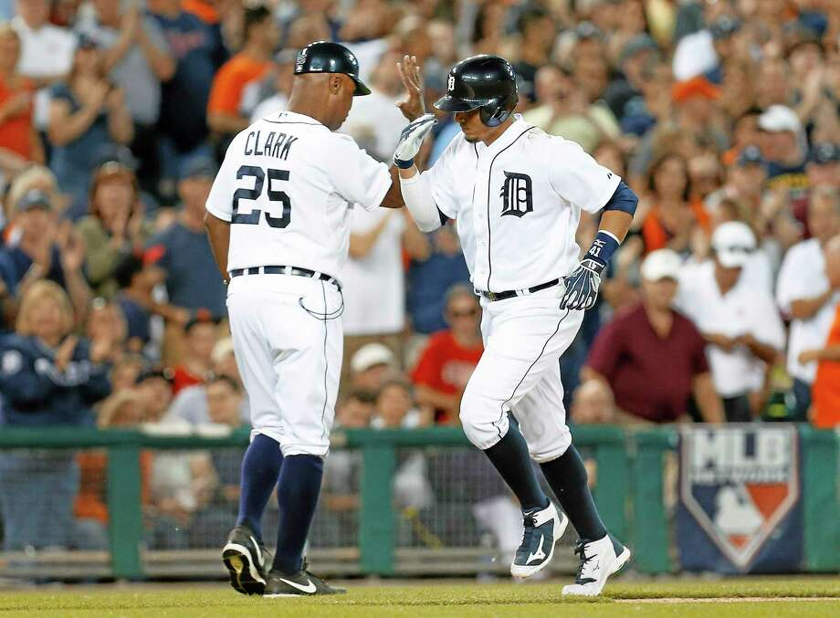 Detroit Tigers' Victor Martinez is congratulated by third base coach Dave Clark (25) after hitting a solo home run against the Boston Red Sox in the eighth inning of a baseball game in Detroit, Friday, June 6, 2014. (AP Photo/Paul Sancya) Photo: AP / AP