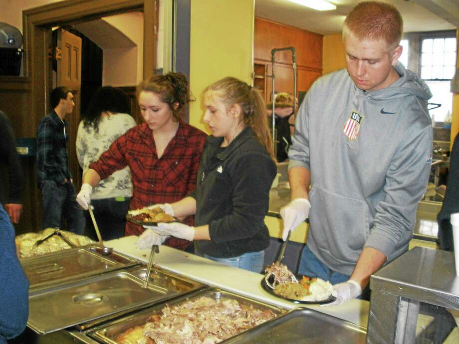 Volunteers help serve the annual Thanksgiving meal at Trinity Church's soup kitchen on Prospect Street in Torrington. The dinner is usually held at Oliver Wolcott Tech, but snow closed the school this week and the church stepped up to host the free dinner. Photo: Stephen Underwood — Special To The Register Citizen