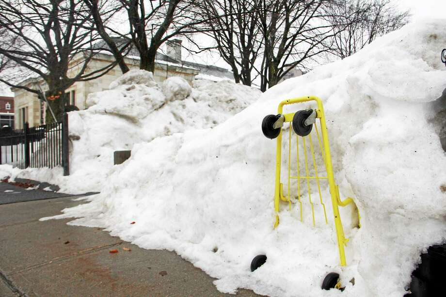 A grocery cart lies buried in a pile of snow more than 3 feet high on Friday, Feb. 21, 2014, in Torrington. The city has spent more than $500,000 in salt to help treat roads, several thousand dollars more than initially budgeted. Photo: Esteban L. Hernandez—Register Citizen