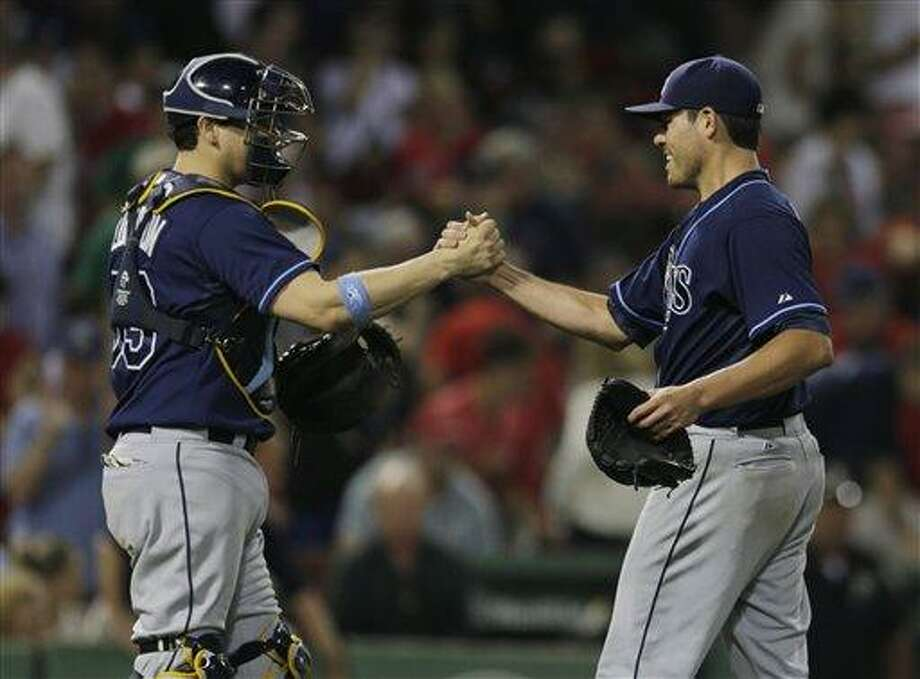 Tampa Bay Rays starting pitcher Matt Moore, right, is congratulated by catcher Jose Lobaton after throwing a complete game and beating the Boston Red Sox in a baseball game at Fenway Park, Monday, July 22, 2013, in Boston. The Rays beat the Red Sox 3-0. (AP Photo/Charles Krupa) Photo: AP / AP