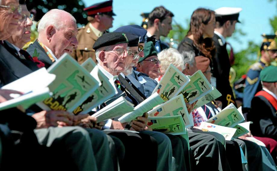 British veterans and other participants attend a French-British D-Day commemoration ceremony at the British War Cemetery in Bayeux, France, Friday, June 6, 2014. World leaders and veterans gathered by the beaches of Normandy on Friday to mark the 70th anniversary of World War Two's D-Day landings. (AP Photo/Thomas Bregardis, Pool) Photo: AP / AFP