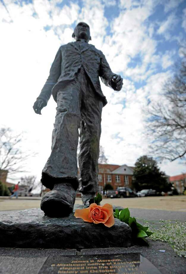A flower is seen on the James Meredith statue at the University of Mississippi in Oxford, Miss., Tuesday, Feb. 18, 2014.  Campus police at the University of Mississippi are checking video surveillance footage in the area around a statue of James Meredith that was found sullied Sunday morning.  (AP Photo/The Daily Mississippian, Thomas Graning) Photo: AP / 2014 Thomas Graning