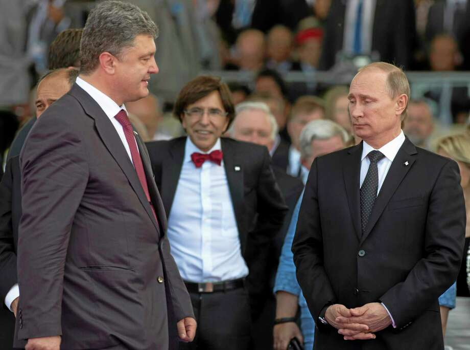 Ukraine's President-elect Petro Poroshenko, left, walks past Russian President Vladimir Putin, right, during the commemoration of the 70th anniversary of the D-Day in Ouistreham, western France, Friday, June 6, 2014. World leaders and veterans prepare to mark the 70th anniversary of the invasion this week in Normandy. (AP Photo/Alexander Zemlianichenko, pool) Photo: AP / AP