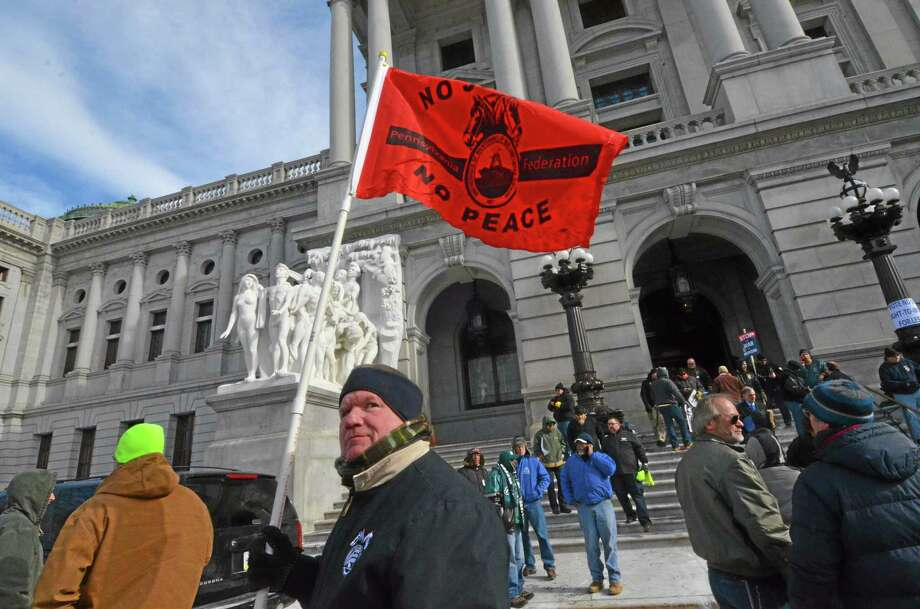 Labor union demonstrators wait outside the Pennsylvania Capitol in the freezing cold after police shut off access to a building already packed with labor union members protesting legislation to prevent the state and local governments from deducting union dues and political action committee contributions from the paychecks of unionized workers, Tuesday, Jan. 28, 2014 in Harrisburg, Pa. (AP Photo/Marc Levy) Photo: AP / AP