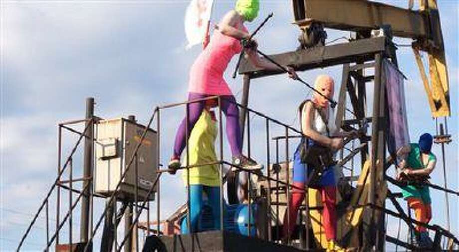 "In this frame grab from handout Pussy Riot new video provided on Tuesday, July 16, 2013, band members in trademark bright-colored ski masks perform on top of an oil rig. Russian provocateurs Pussy Riot are back in action, releasing their first music video since three members went to prison last year for a prank denouncing Vladimir Putin. The video shows band members in trademark bright-colored ski masks and short skirts, cavorting and shrieking atop an oil rig. Backed by hectic guitar and a drum fusillade, they pour oil on a large photo of state oil giant Rosneft's chairman and liken Putin to an Iranian ayatollah. One member of the collective, who gave only her stage name of Grelka, said after the video's Tuesday release that ""the main message is that Putin has spread the country's wealth among his friends."" Three members were sentenced to two years for an anti-Putin ""punk prayer"" in Moscow's main cathedral. One was later released on probation. (AP Photo/Pussy Riot) Photo: AP / Pussy Riot"