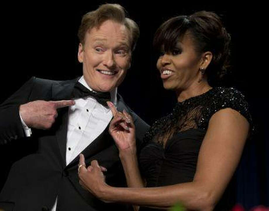 First lady Michelle Obama and late-night television host and comedian Conan O'Brien's gesture to his his tie at the White House Correspondents' Association Dinner at the Washington Hilton Hotel, Saturday, April 27, 2013, in Washington. (AP Photo/Carolyn Kaster) Photo: AP / AP