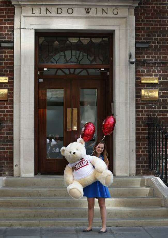 """A girl poses for the photographers with an oversized teddy bear as part of a publicity stunt for a magazine outside St. Mary's Hospital exclusive Lindo Wing in London, Thursday, July 18, 2013. Dozens of reporters have already staked out the central London hospital where the Duchess of Cambridge is expected to give birth. The Palace has said only that Kate is due to deliver the baby in """"mid-July."""" (AP Photo/Lefteris Pitarakis) Photo: AP / AP"""