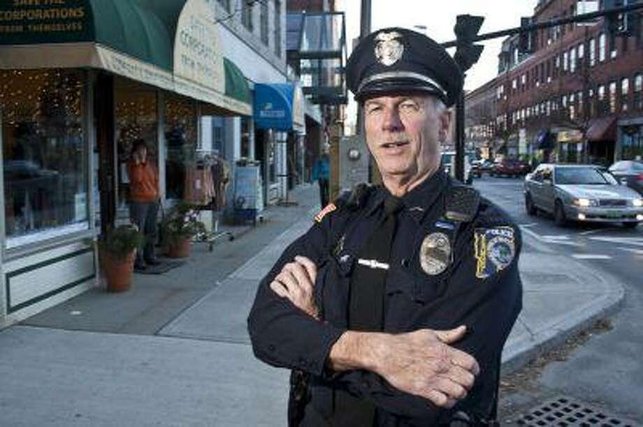 """Officer John """"Zippo"""" Frechette stands on Main Street in Brattleboro on one of his last days on the Brattleboro Police Department before retiring."""
