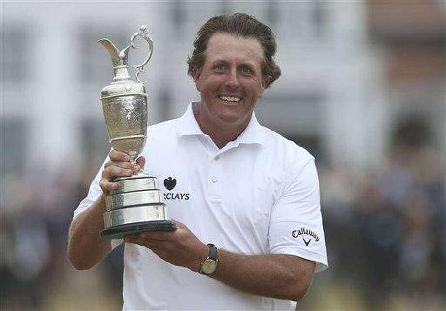 Phil Mickelson of the United States holds up the Claret Jug trophy after winning the British Open Golf Championship at Muirfield, Scotland, Sunday July 21, 2013.  (AP Photo/Scott Heppell) Photo: AP / AP