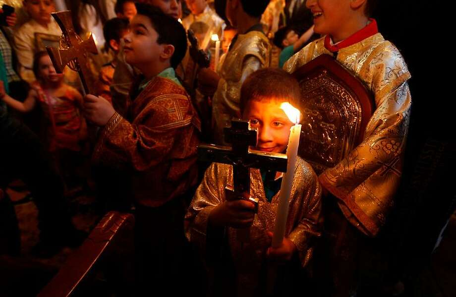 Christian youths are seen during a Palm Sunday service at a Greek Orthodox church in Gaza City, Sunday, April 28, 2013. Palm Sunday marks for Christians, Jesus Christ's entrance into Jerusalem, when his followers laid palm branches in his path, prior to his crucifixion. (AP Photo/Hatem Moussa) Photo: AP / AP