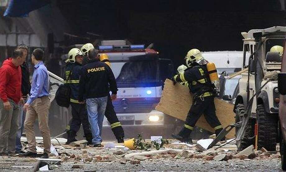 Policemen and firefighters inspect the scene of an explosion in downtown Prague, Czech Republic, Monday, April 29, 2013.  Police said a powerful explosion has damaged a building in the center of the Czech capital and they believe some people are buried in the rubble. (AP Photo/Petr David Josek) Photo: ASSOCIATED PRESS / AP2013