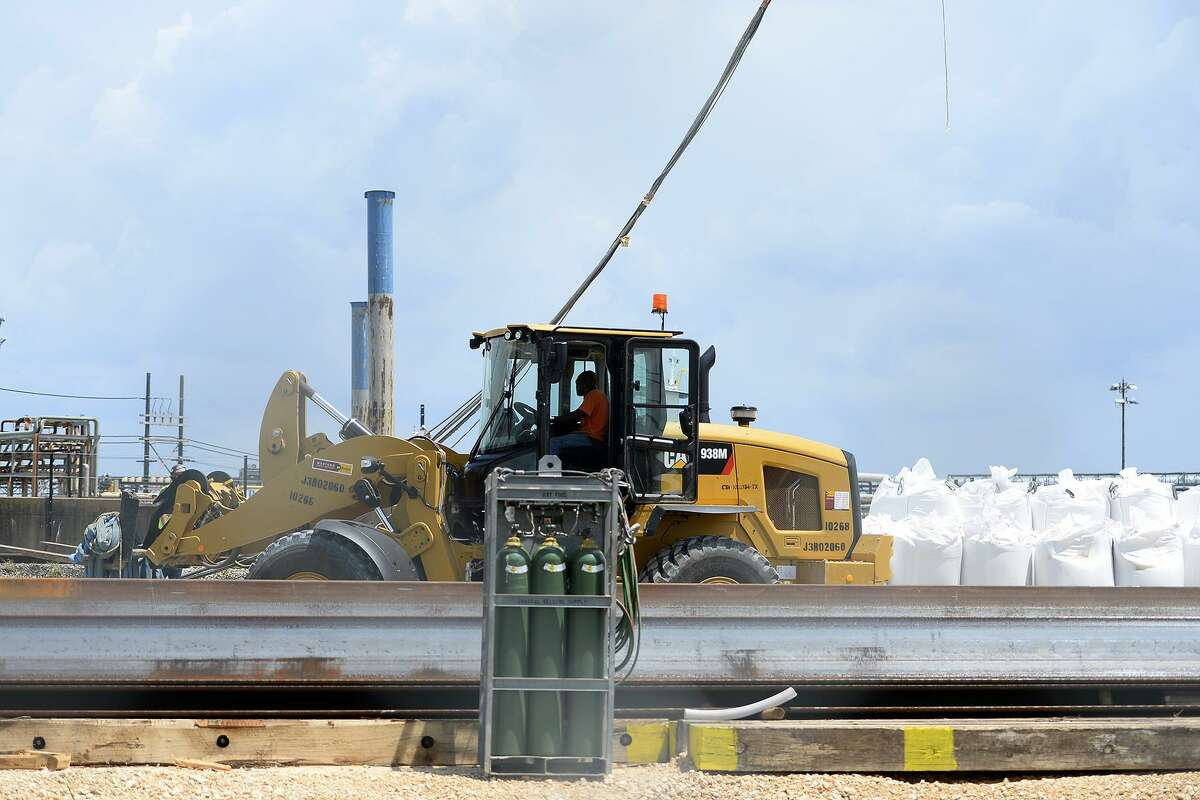 Workers build a wall of sandbags along the damaged levee near the Valero Port Arthur refinery in preparation for Hurricane Harvey on Thursday.