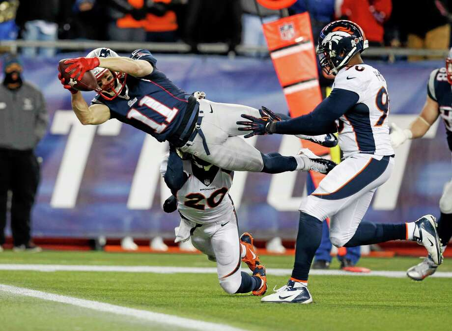 New England Patriots wide receiver Julian Edelman (11) scores a against touchdown Denver Broncos strong safety Mike Adams (20) and defensive end Shaun Phillips (90) in the fourth quarter of an NFL football game Sunday in Foxborough, Mass. Photo: Elisa Amendola — The Associated Press  / AP