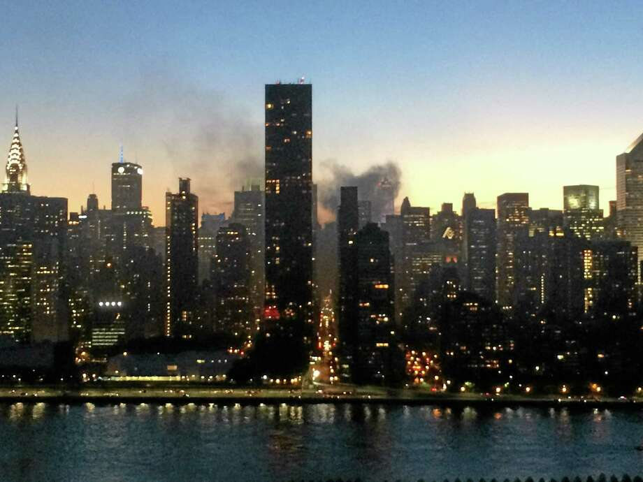 In this mobile phone photo provided by Cat Chung, smoke rises from a fire at a building near Manhattan's Rockefeller Center on Friday, June 6, 2014, as seen from Long Island City in the Queens borough of New York. The FDNY says the fire broke out around 8:45 p.m. in the basement and ventilation system of 604 5th Avenue between 48th and 49th Streets. Photo: (Cat Chung — The Associated Press)  / AP