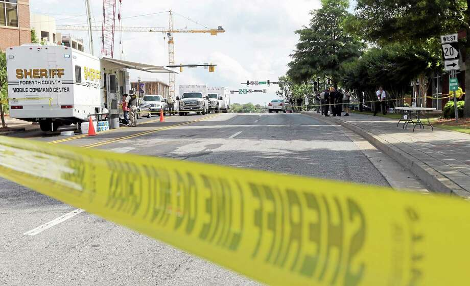 Crime scene tape blocks a road near the Forsyth County Courthouse in Cumming, Ga., on Friday afternoon, June 6, 2014. Earlier Friday, a man wielding an assault rifle, explosives and supplies to take hostages opened fire outside the courthouse, wounding a deputy before he was killed in a shootout with officers, authorities said. Photo: (Ben Gray — The Associated Press)  / The Atlanta Journal-Constitution