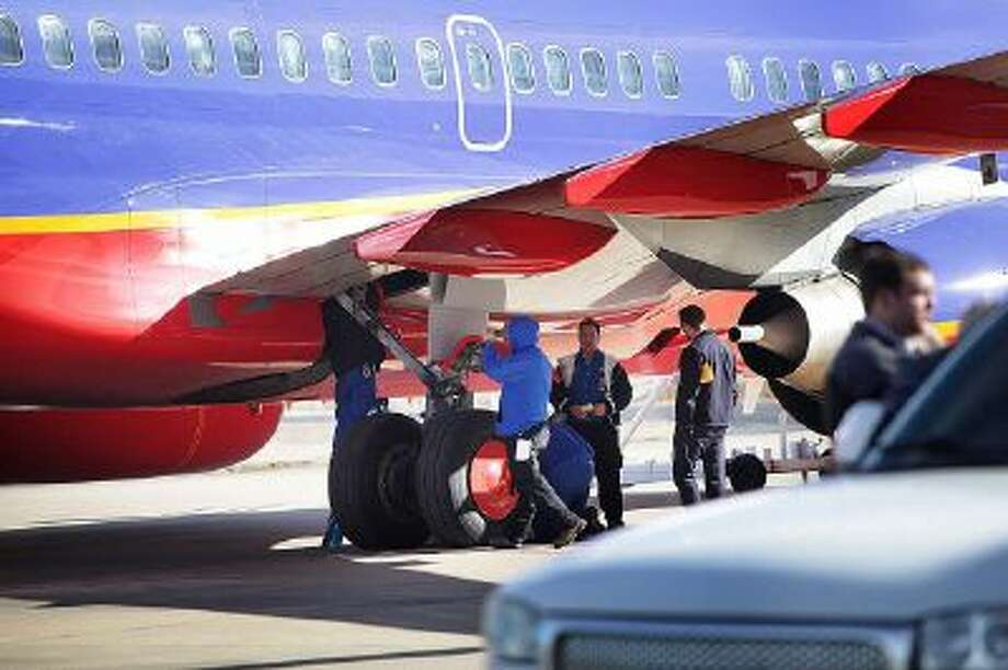 A crew inspects Southwest Airlines Flight 4013 at the M. Graham Clark Airport in Hollister, Mo. Monday, Jan. 13, 2014.