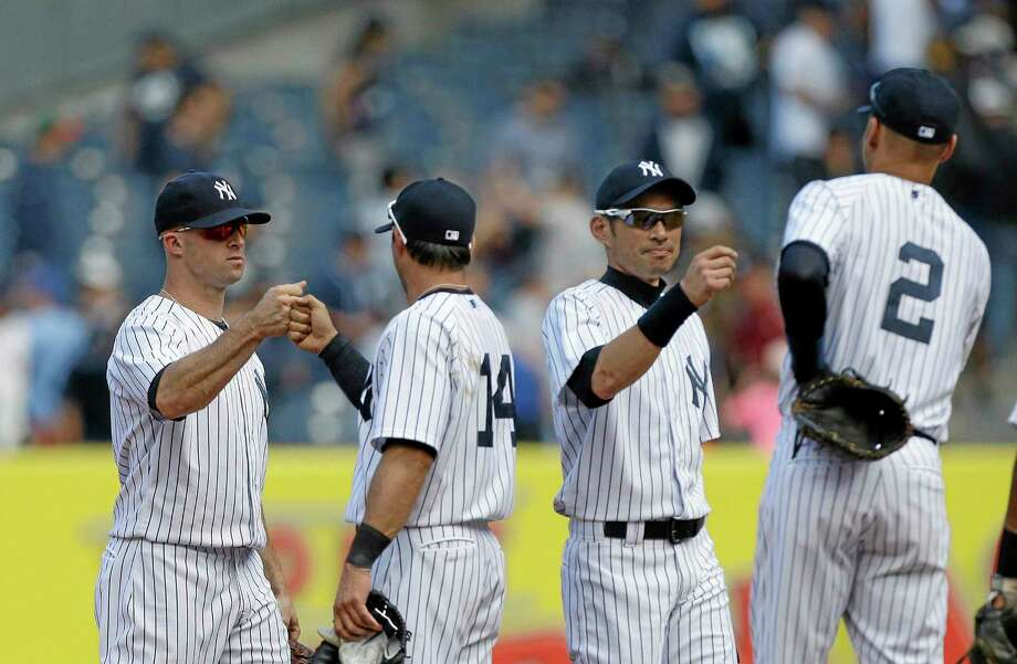 Yankees Brett Gardner, left, and Ichiro Suzuki, second from right, celebrate with teammates after Thursday's 2-1 win over the Oakland Athletics in New York. Photo: Frank Franklin II — The Associated Press  / AP