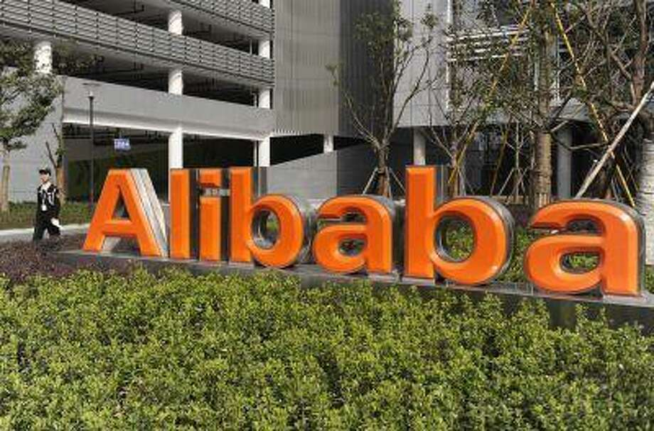 A security guard walks past a logo of Alibaba Technology Co. Ltd at its headquarters on the outskirts of Hangzhou, Zhejiang province March 16, 2010. / X02089