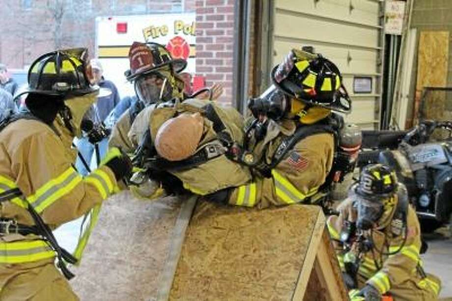 JASON SIEDZIK/Register Citizen -- Winsted Fire Department firefighters Dave Hull, Phil Bascetta, Pat Matthews and Nick Sartirana conduct an RIT, or Rapid Entervention Team, drill during the department's open house Monday night.