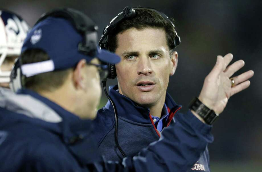 UConn head coach Bob Diaco talks to an assistant during the second quarter of the Huskies' 41-0 loss to Cincinnati on Saturday at Rentschler Field in East Hartford. Photo: Michael Dwyer — The Associated Press  / AP