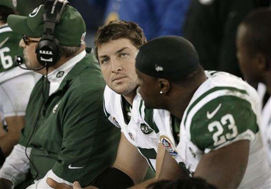 New York Jets quarterback Tim Tebow, center, looks at the scoreboard in the fourth quarter of an NFL football game against the Tennessee Titans on Monday, Dec. 17, 2012, in Nashville, Tenn. The Titans won 14-10. At right is running back Shonn Greene (23). (AP Photo/Wade Payne) Photo: ASSOCIATED PRESS / AP2012